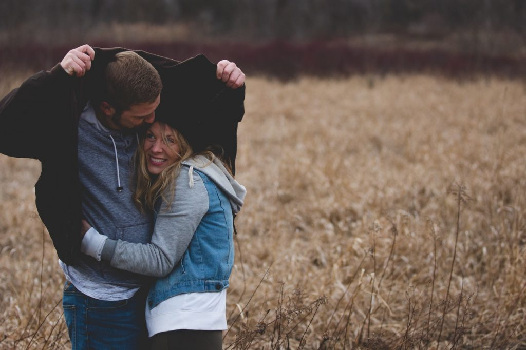 couple embracing in a field protecting themselves from the rain with a jacket, loving look