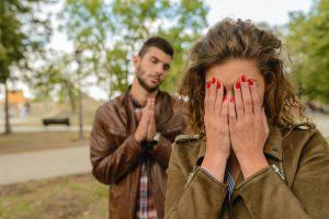 Femme triste avec un homme derrière lui suppliant de lui pardonner