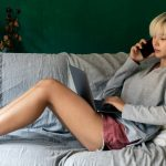 Woman sit on her sofa, and look her cumputer and phone